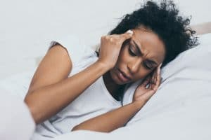 pretty african american woman suffering from headache while lying in bed