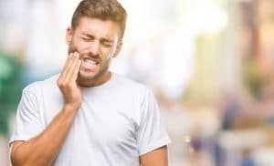 Young handsome man over isolated background touching mouth with hand with painful expression because of toothache or dental illness on teeth. Dentist concept.